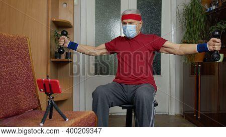 Senior Elderly Caucasian Man In Sportswear In Living Room, Making Weightlifting Dumbbells Exercising