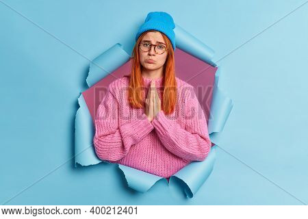Displeased Redhead Woman Presses Palms Together Looks With Imploring Pleading Face Expression Asks F