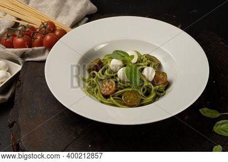 Green Pesto Paste. Boiled Spaghetti With Pesto Sauce, Cherry Tomatoes, Basil And Mozzarella Cheese.