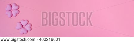 Red Wooden Hearts On The Left Border On A Pink Wooden Background With Space For Text