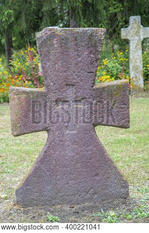 A Worn Sandstone Grave Marker In The Shade On A Very Bright Day. There Is No Text Visible On The Sto