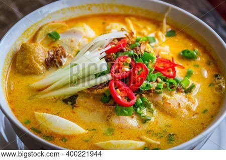 A Bowl Of Laksa Rice Noodles In Mild Curry Gravy With Hard Boiled Egg Bean Sprouts, Scallions, Tofu