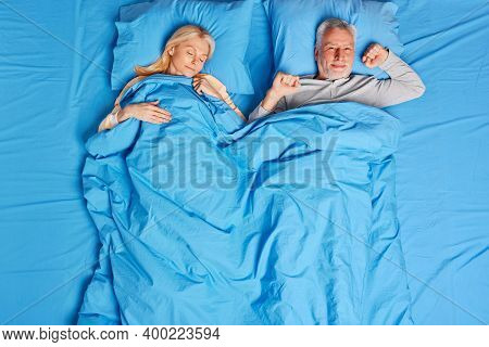 Glad Bearded Mature Man Stretches In Bed Feels Pleasure After Healthy Sleep. Beautiful Middle Aged W