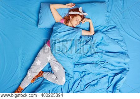Top View Of Lovely Redhead Teenage Girl Sleeps Deeply On Comfortable Bed In Funny Pose On Back Sees