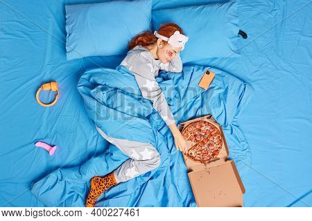 Photo Of Lazy Woman In Nightwear Has Breakfast In Bed Eats Delicious Pizza Spends Weekend At Home Po