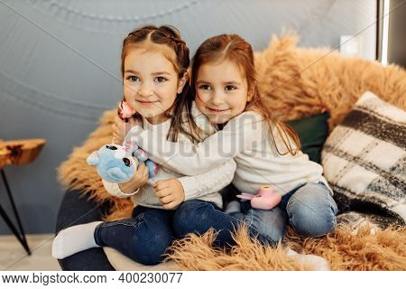 Portrait Of Adorable Sisters Sitting On The Couch, Smiling. Beautiful Little Girls Cuddling, Playing