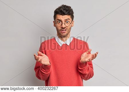 Indignant Puzzled Man Raises Palms And Faces Difficult Choice Feels Hesitant Wears Round Transparent