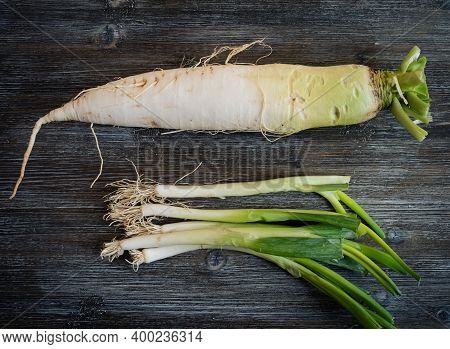 Daikon Root And Scallions On A Rustic Wooden Table.