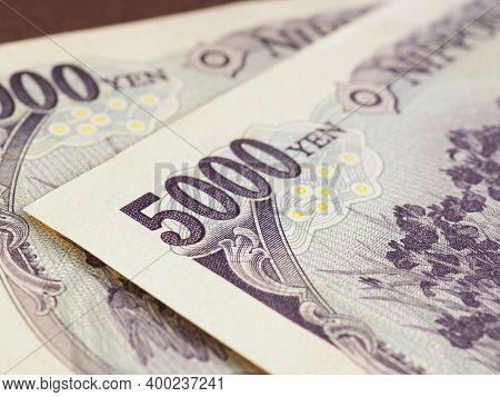 Japanese 5000 Yen Bills Lie On A Brown Surface Close Up. An Illustration On The Theme Of Banks, Fina