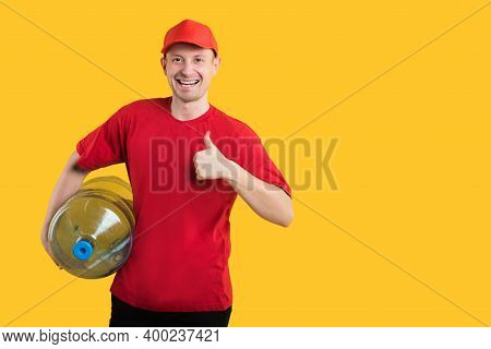 Water Delivery. Happy Courier In Red Uniform On Yellow Background With Bottle Of Water Showing Thumb