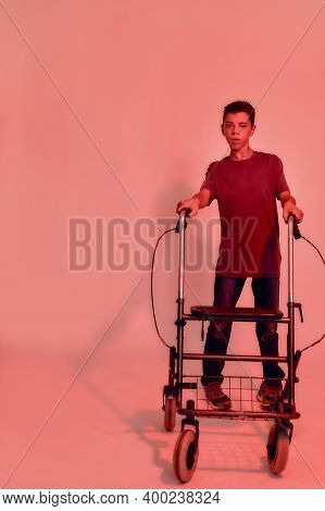 Full Length Shot Of Teenaged Disabled Boy With Cerebral Palsy Looking At Camera, Taking Steps With H