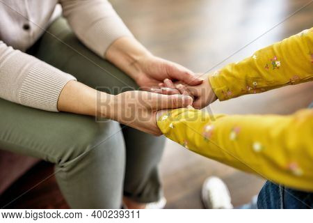 Support. Close Up Shot Of Grandmother And Little Granddaughter Holding Hands Together While Spending