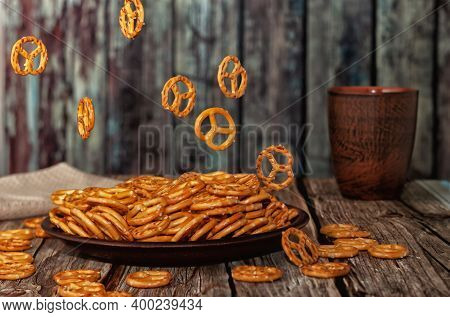 Small Pretzel Shaped Cookies Falling Into A Clay Bowl, Wooden Background, Food Levitation