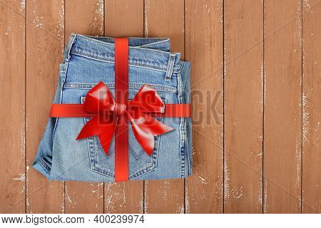 Clothes, Shoes And Accessories - Top View Gift Tied Red Bow Blue Jeans On A Wooden Background