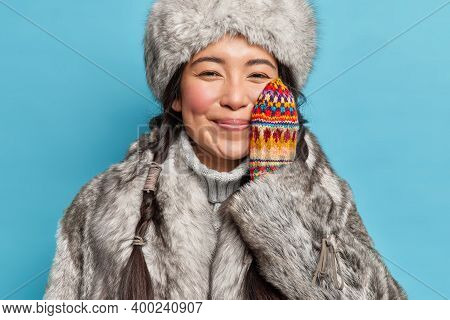 Cheerful Tender Eskimo Woman Wears Winter Clothes Keeps Hand On Cheek Enjoys Winter Time Smiles Glad