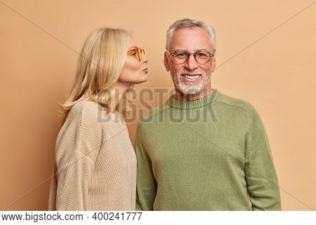 Horizontal Shot Of Affectionate Blonde Aged Woman Kisses Husband In Cheek Expresses Affection And Te