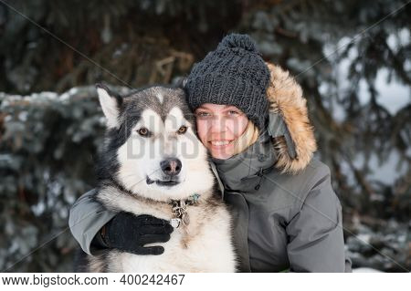 Happy Woman Embracing Alaskan Malamute In Winter Forest. Close Up.