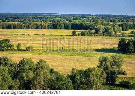 Summer Rural Landscape With Sheafs Of Hay On Agriculture Fields, Forest And Windmills On Windfarm, C