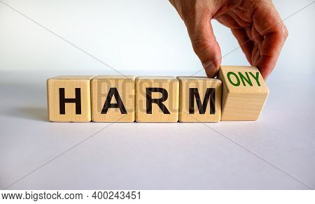 From Harm To Harmony. Male Hand Turns The Cube And Changes Word 'harm' To 'harmony'. Beautiful White