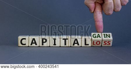 Capital Loss Or Gain Symbol. Male Hand Turns Cubes And Changes Words 'capital Loss' To 'capital Gain