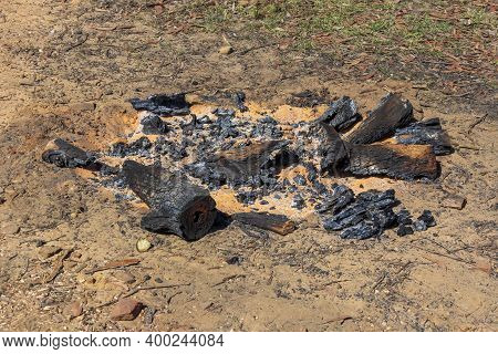 Burnt Wood And Coals From A Recent Campfire On Brown Dirt In The Blue Mountains In Regional New Sout