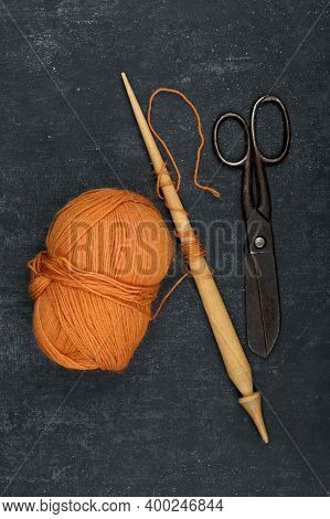 Tangle Of Orange Color Woolen Yarn, Old Rusty Tailor Scissors And Spindle, Close-up