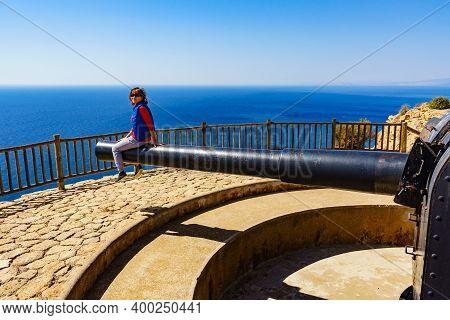 Tourist Attraction. Woman At Battery De Castillitos In Spain Cartagena, Cabo Tinoso. Military Cannon