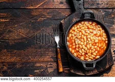 Beans In Tomato Sauce In A Pan. Dark Wooden Background. Top View. Copy Space