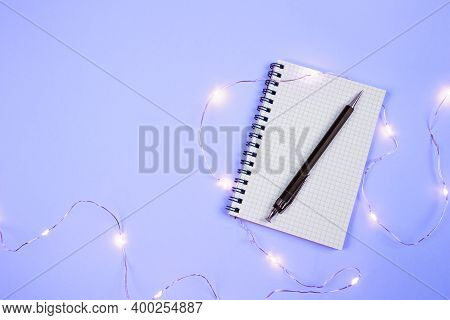 Blank Notepad Page With Pen And New Year Lights On Purple Background. Holiday Business Card With Cop