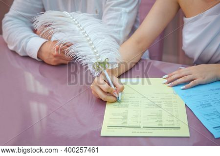 Groom And Bride Register Marriage. Woman Puts His Signature On Wedding . A Womans Hand Signs And Reg