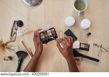 Top View Closeup Of Female Hands Holding Eyeshadow Pallete Over Table With Various Beauty Products W