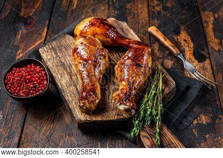 Bbq Grilled Chicken Drumsticks On A Wooden Cutting Board. Dark Wooden Background. Top View