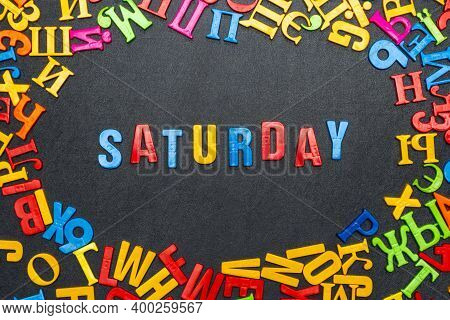 Saturday Word Made Of Bright Colored Letters On Black Background.