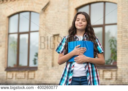 Cute Dreamy Kid With Long Hair In Casual Style Hold School Book Keeping Eyes Closed In Schoolyard, D