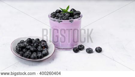 Tasty Fresh Blueberry Yoghurt Shake Dessert In Glass Standing On White Table Background. Homemade Be