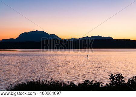 Stand Up Paddle At Lake Faaker See In Carinthia, Austria. Beautiful Sunset In Front Of Dobratsch Mou