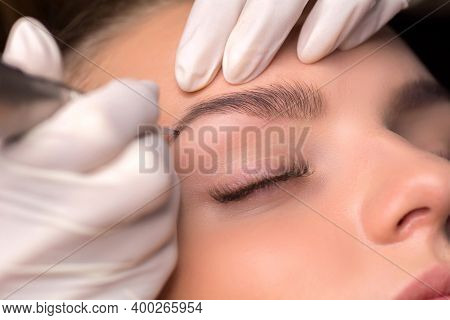 Permanent Eyebrow Makeup. Cosmetologist Applying Tattooing Of Eyebrows.