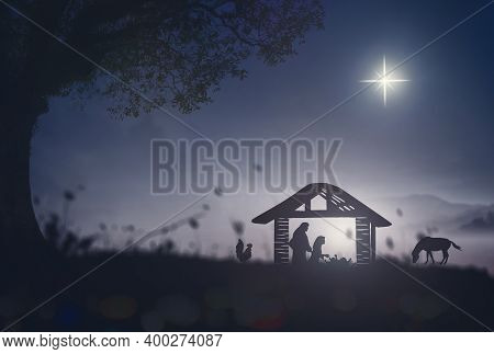 Christmas Religious Nativity Concept: Silhouette Mother Mary, Joseph And Jesus In The Manger