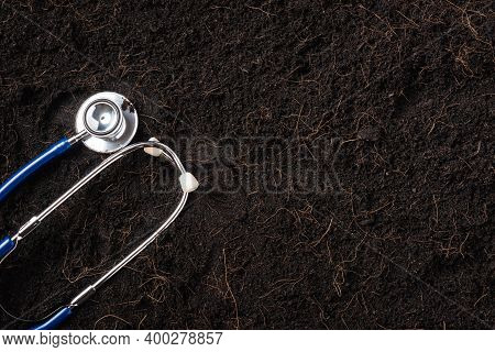 Black Land For Plant Background And Doctor Stethoscope, Top View Of Handprint On Fresh Soil With Mul