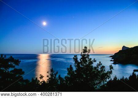 Summer moonlit night. Lunar path in the sea or ocean. A magical, fabulous, romantic night.
