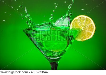 Green drink in a glass. Green water or limnad. A splash of green liquid similar to absinthe. Alcohol and alcoholism.