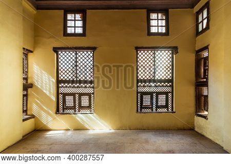Facade Of Two Interleaved Grunge Wooden Ornate Windows - Mashrabiya - In Stone Wall In Abandoned Bui