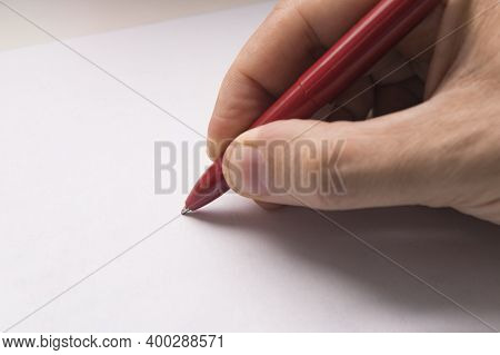 Top View Of Male Hand With Pencil On Blank Paper Sheet. On Cardboard Background. A Mans Hand Writes