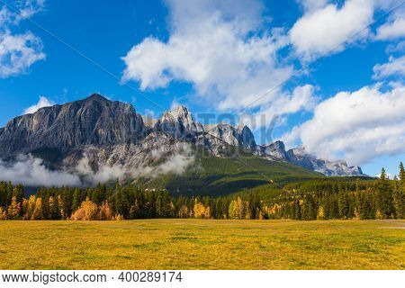 Lush bright autumn day in the Canadian Rockies. The majestic Rocky Mountains. The Three Sisters Mountain is covered in lush white clouds. The concept of active, ecological and photo tourism