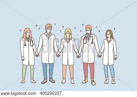 Doctors Teamwork, Uniting Efforts Against Covid-19 Pandemic Concept. Group Of Young Doctors In Prote
