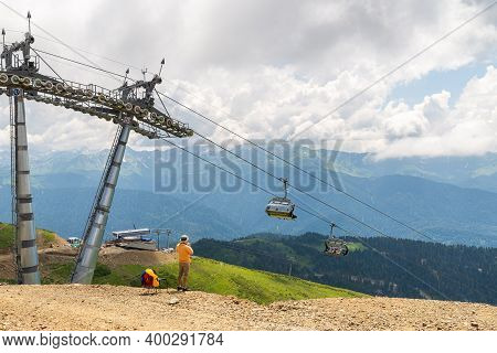 Man Make A Photo Of Chairlift In A Mountain Region In Summer.