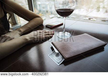 A Hundred Dollars Generous Tip On The Table In A Leather Folder. The Girl Drank The Wine And Paid Th