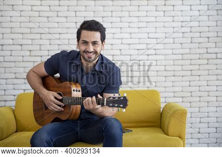Lifestyle Portrait Of Attractive Handsome Man With Pleasant Smile Relaxing And Sitting Play Guitar A