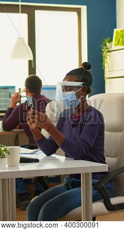 Black Businesswoman Browsing Using Smartphone Sitting In Office Room Wearing Face Mask And Visor Whi