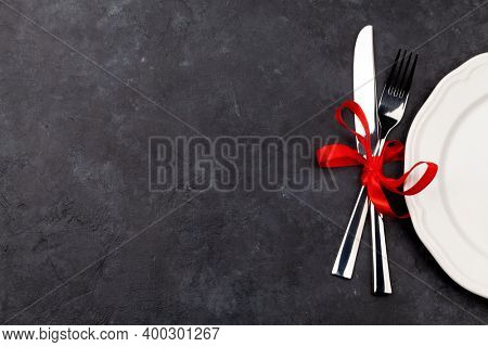 Valentines day with empty plate and silverware. Top view flat lay with copy space